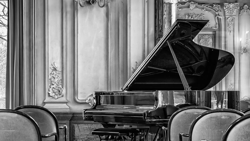 Sala de conciertos vacía con piano en escenario