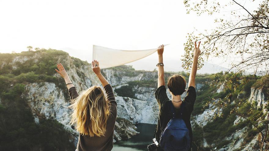 Dos chicas de espaldas levantando un pañuelo en paisaje de montaña