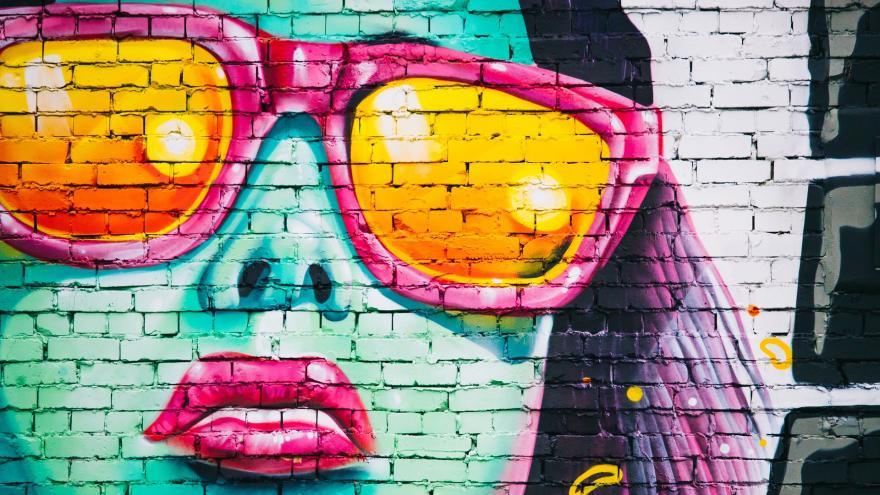 Grafitti en una pared de la cara de una chica con gafas