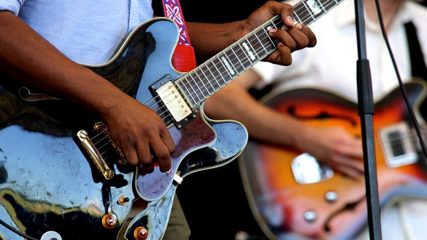 Imagen de las manos de dos personas tocando guitarras eléctricas