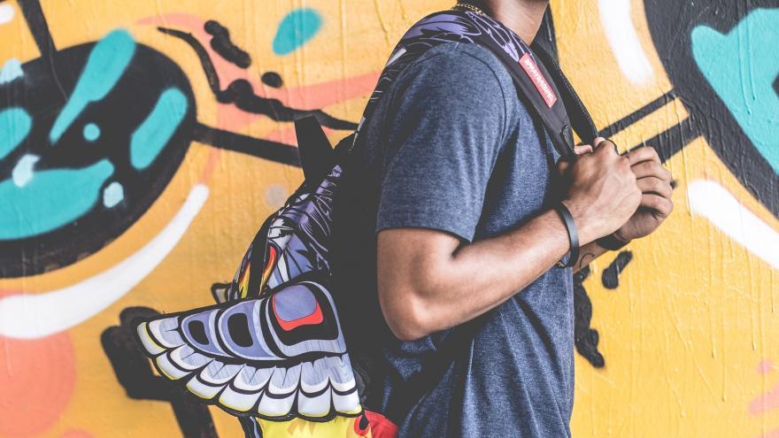 Chico con una mochila con graffiti de fondo