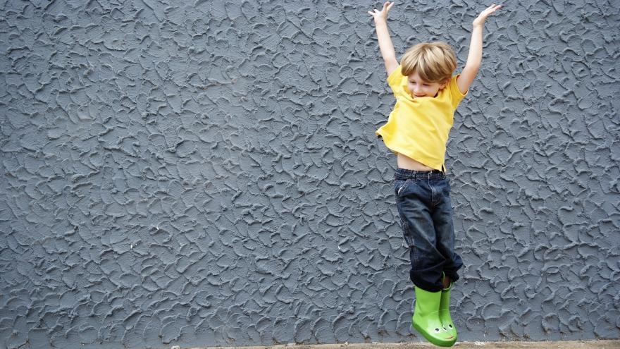 Niño contento saltando en una acera