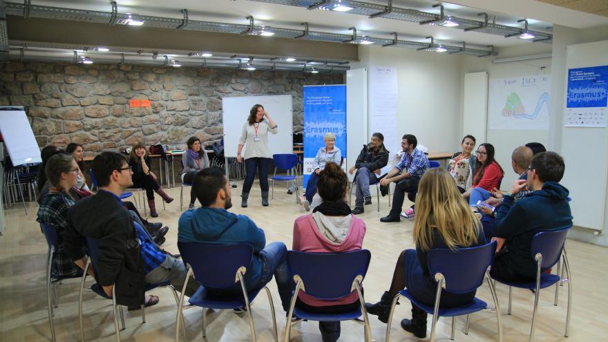 Jóvenes reunidos en círculo con profesora de pie