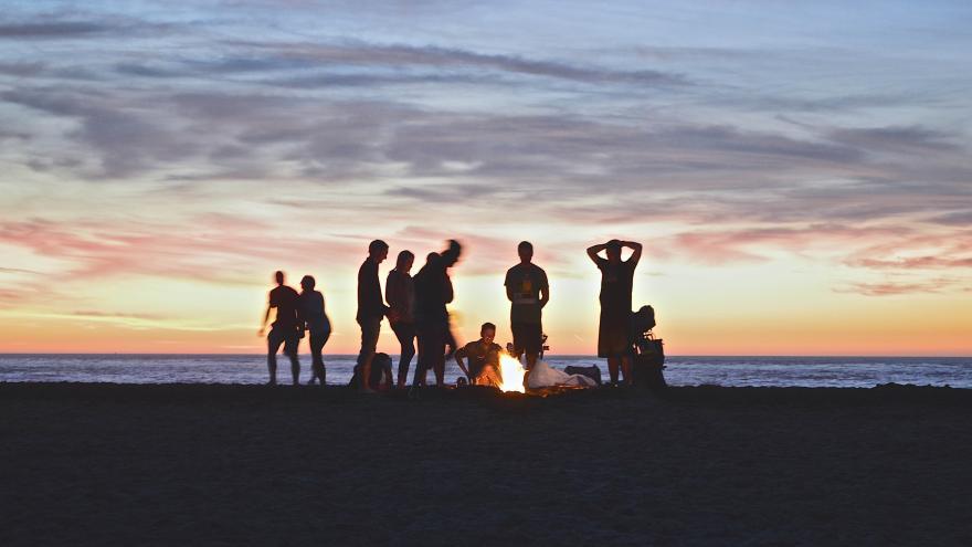 Jóvenes reunidos en la playa al atardecer