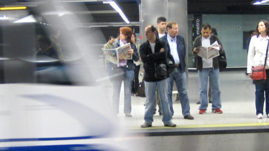 Personas esperando en andén mientras el metro entra en la estación