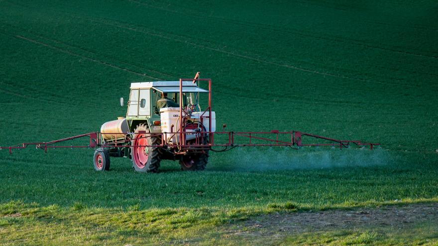 Tractor con aplicador de pesticidas en un campo verde