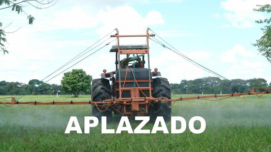 Tractor fumigando un campo con un cartel de aplazado en blanco