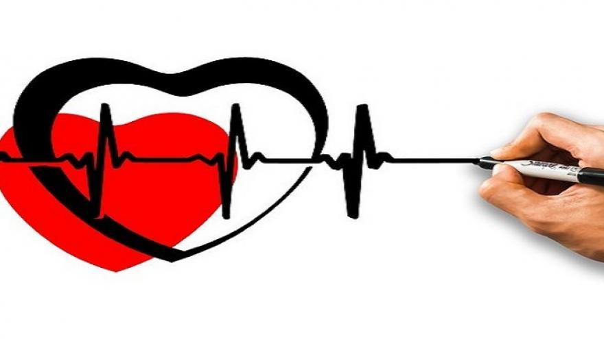 Mano dibujando una línea de electrocardiograma encima de un corazón