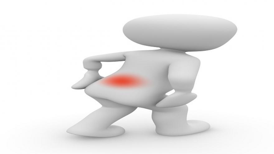 Muñeco con punto rojo en la espalda y gesto de dolor