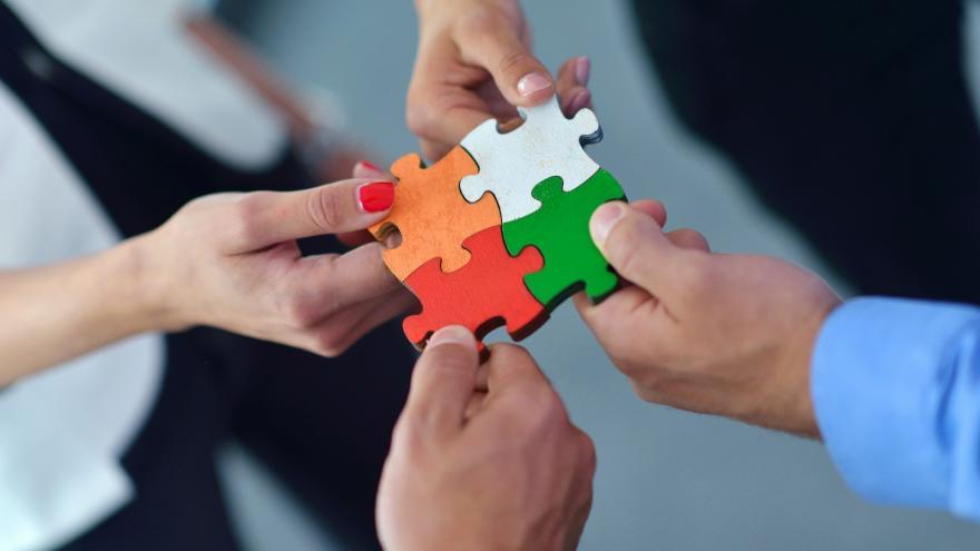 Grupo de personas ensamblando un rompecabezas que representa el concepto de trabajo, equipo y consenso