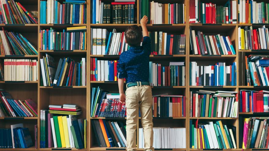 Niños seleccionando un libro en una biblioteca