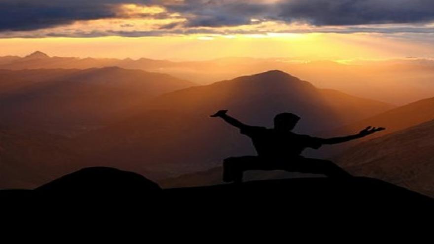 Persona haciendo taichi al atardecer con montaña al fondo
