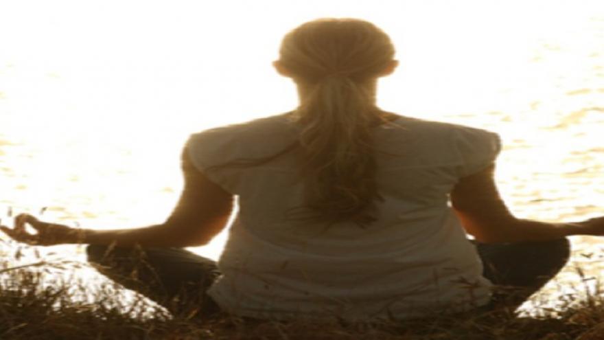 Mujer meditando sentada mirando al sol