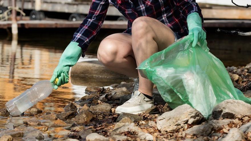 Recoger botella rio bolsa basura