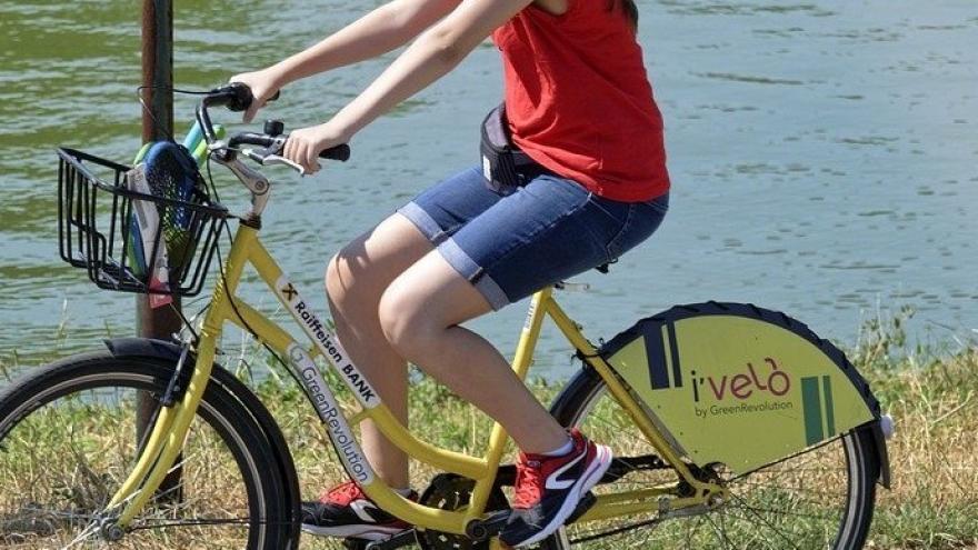 Niña paseando en bicicleta junto al arroyo