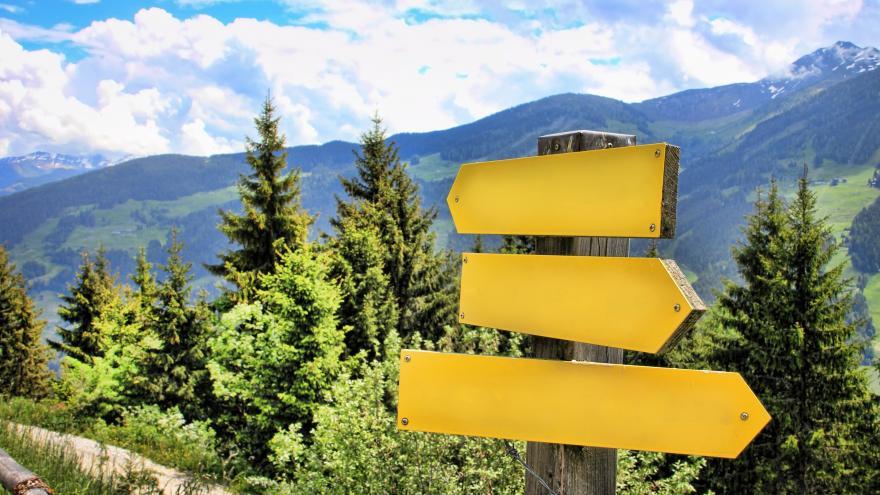 Paisaje con montañas, árboles y dos flechas amarillas que indican dos direcciónes