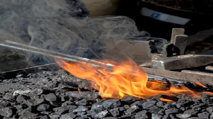 Forja de carbón con barra de hierro en el fuego