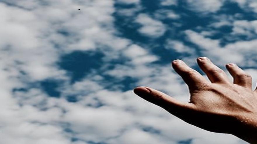Mano abierta con cielo de fondo