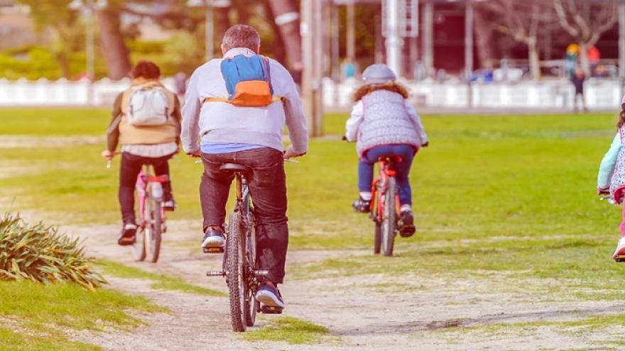 Grupo de cuatro personas de espaldas montando en bici