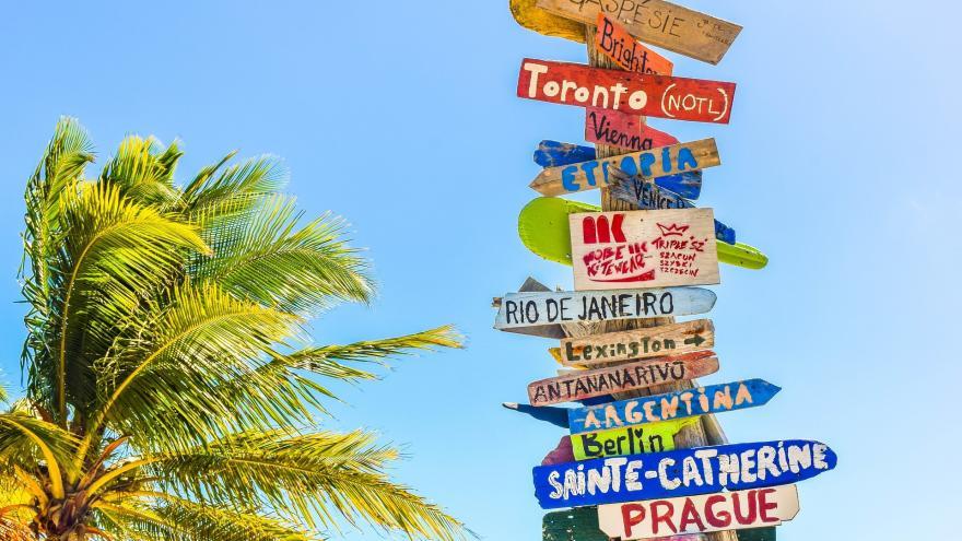 Poste de madera con señales indicativas de ciudades