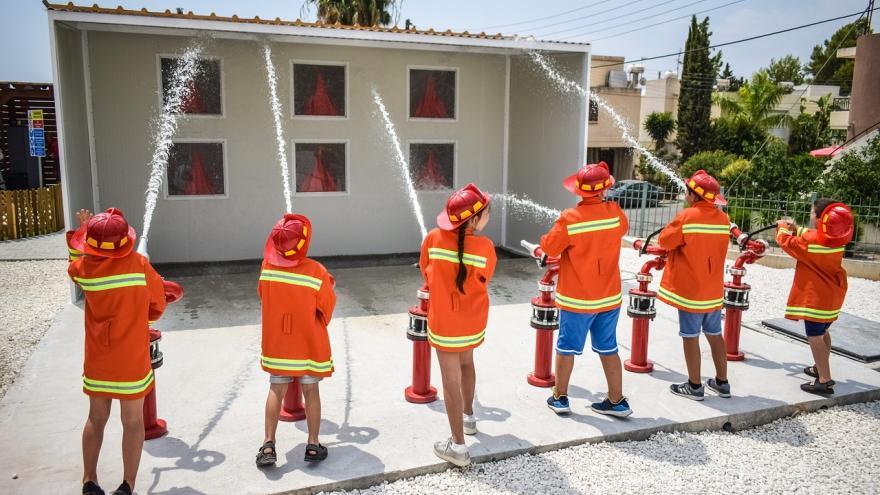 Niños manguera vestidos bomberos