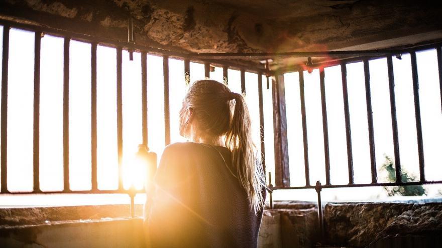 Chica entre barrotes luz del sol