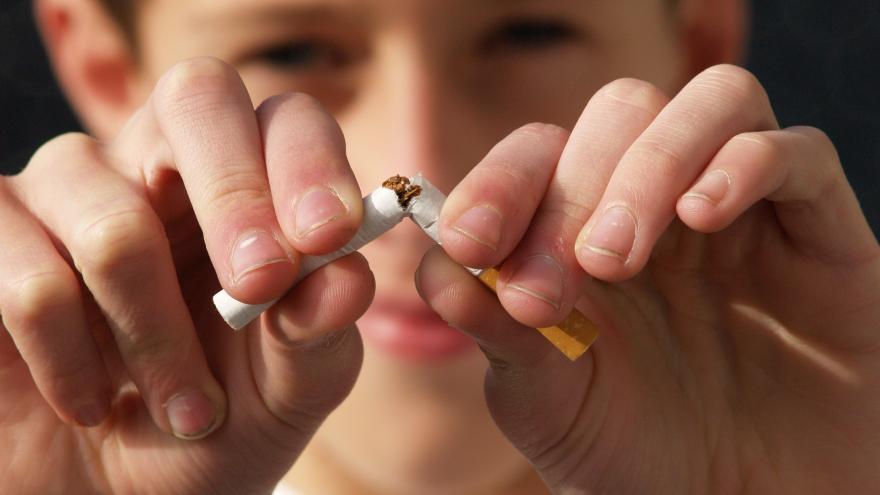 Joven rompiendo un cigarrillo