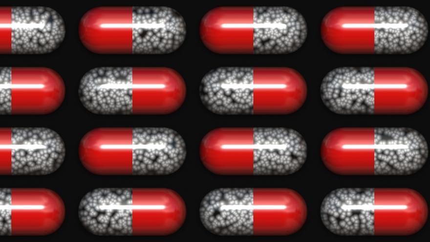 Cápsulas bicolores (rojas y negras) simbolizando antibióticos