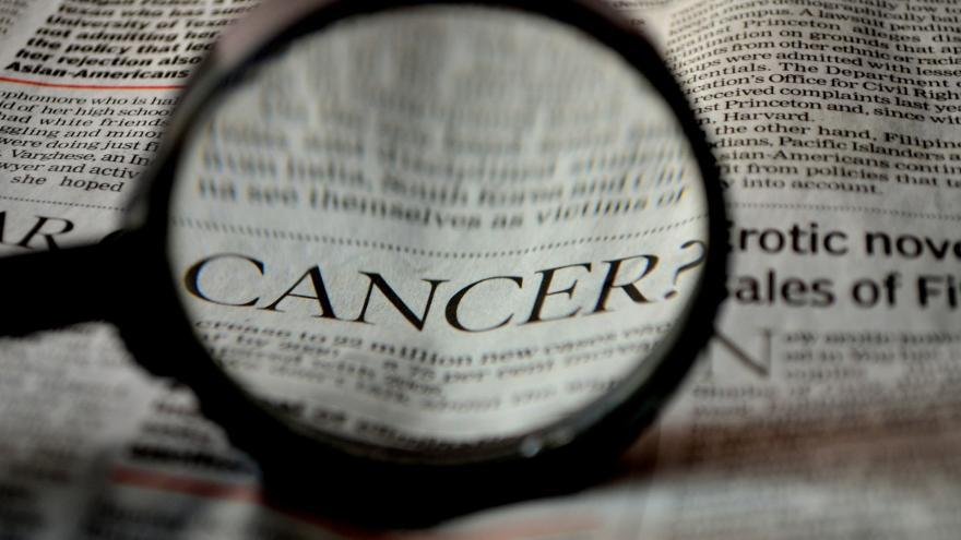 """lupa aumentando la palabra """"cáncer"""" en un periódico"""