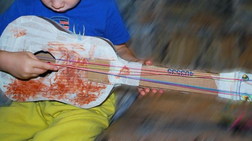 Niño tocando guitarra cartón gomas
