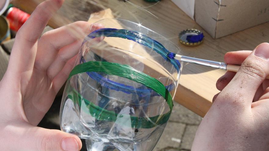 Manos pintando botella de plástico