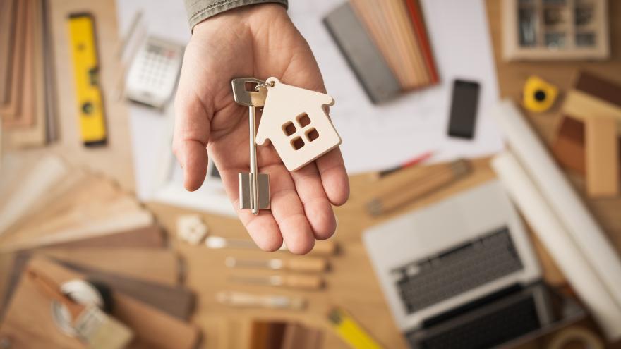 Mano con una llave y un llavero de una casa