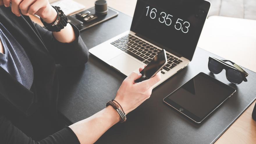 Imagen de una persona con un teléfono móvil, un ordenador y una tablet