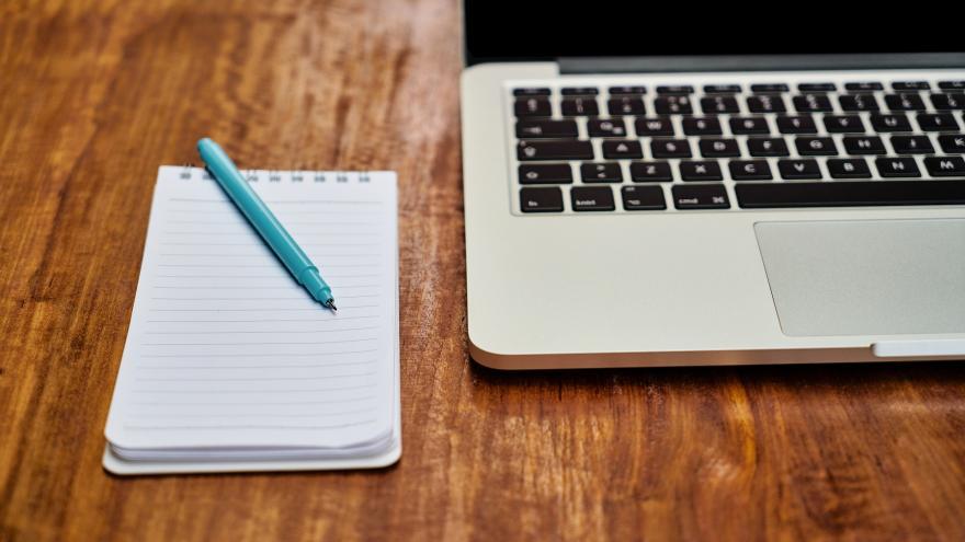Un bloc para tomar notas junto a un ordenador portatil