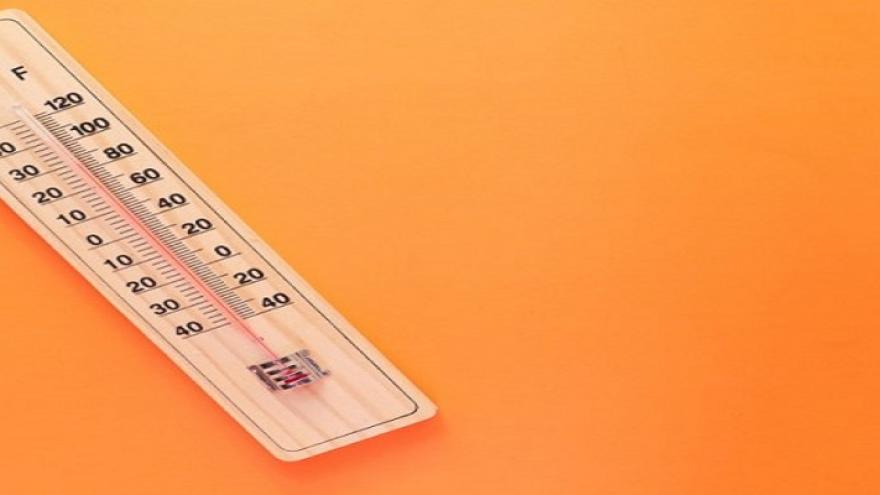 Termómetro de mercurio y madera con un fondo naranja