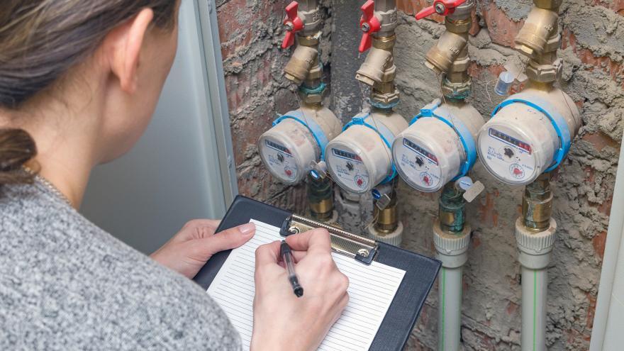Una mujer midiendo un contador de agua