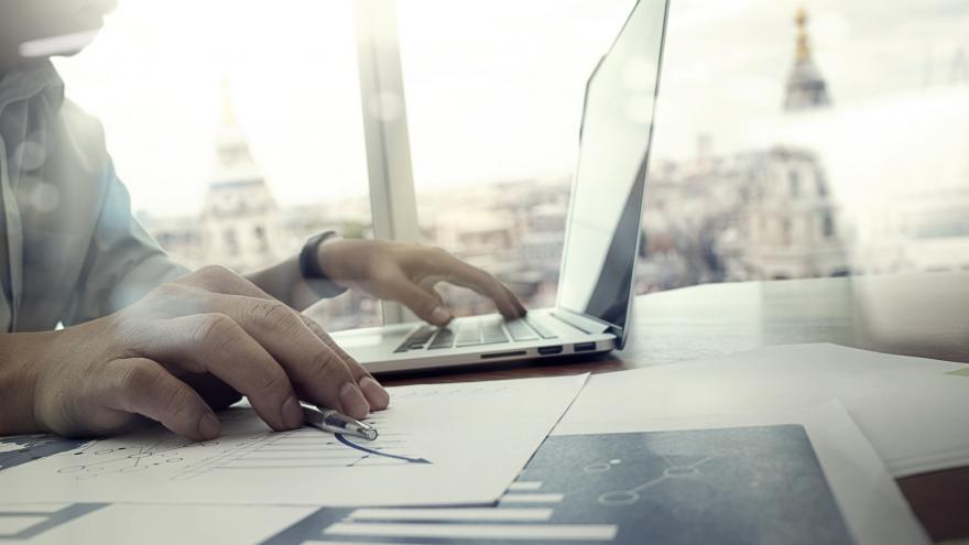 Manos de un hombre tecleando en un ordenador portatil con la ciudad de fondo