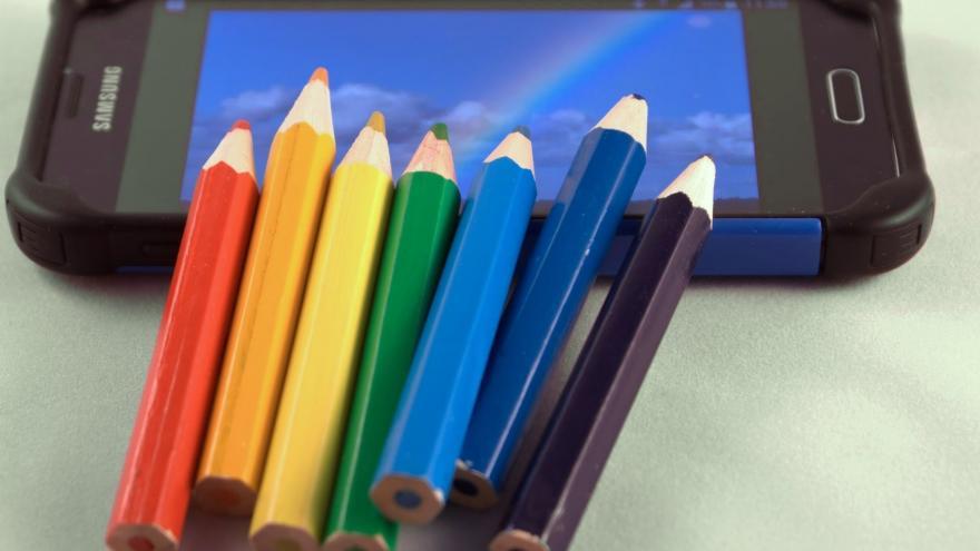 Imagen de unos lapiceros de colores sobre un teléfono móvil