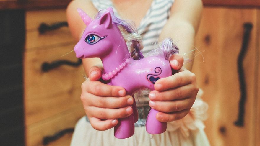Niña ofreciendo un unicornio de jueguete