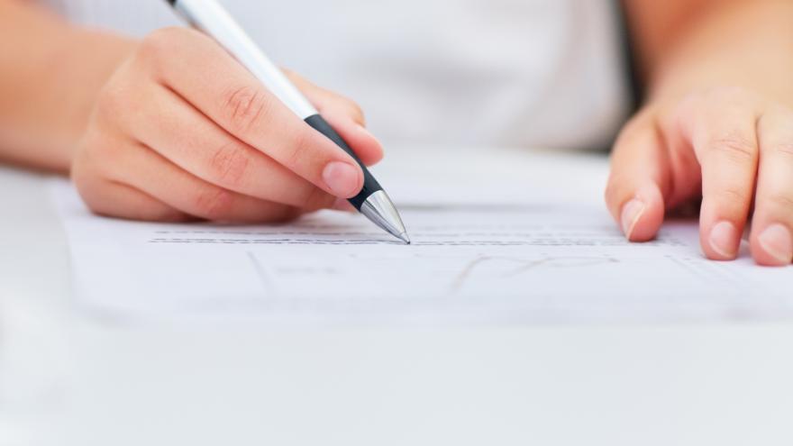 Persona escribiendo en un folio