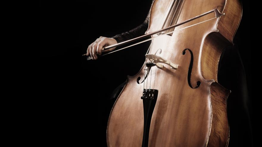 Persona tocando el violonchelo sobre un fondo negro