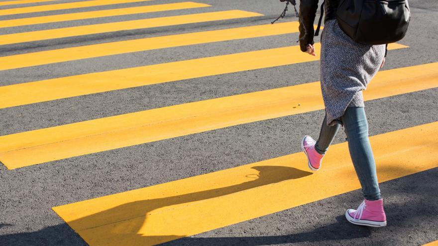 Joven cruzando paso de cebra rayas amarillas
