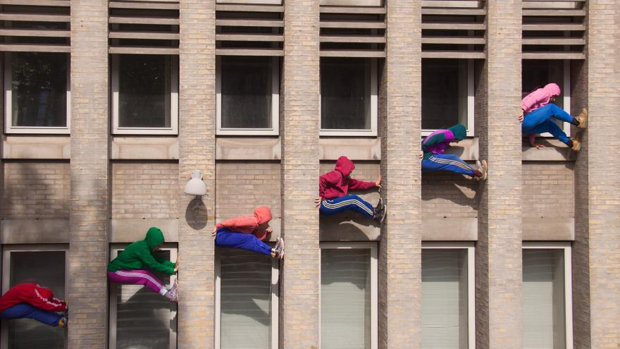 Grupo de jóvenes subidos en las ventanas de un edificio