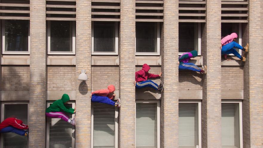 Jóvenes subidos a la pared de un edificio