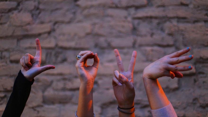 Imagen de cuatros manos componiendo las letras de la palabra amor