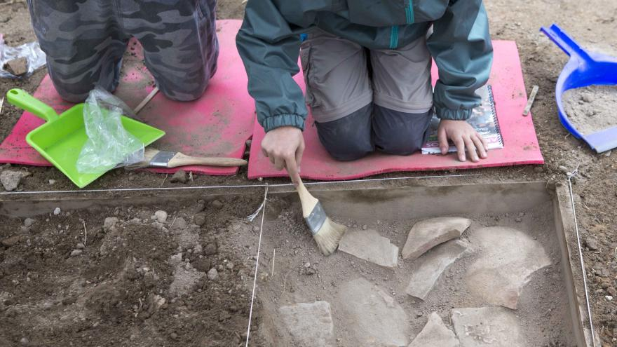 Niños arrodillados en una imitación de yacimiento arqueológico limpiando restos de cerámicas con unas brochas