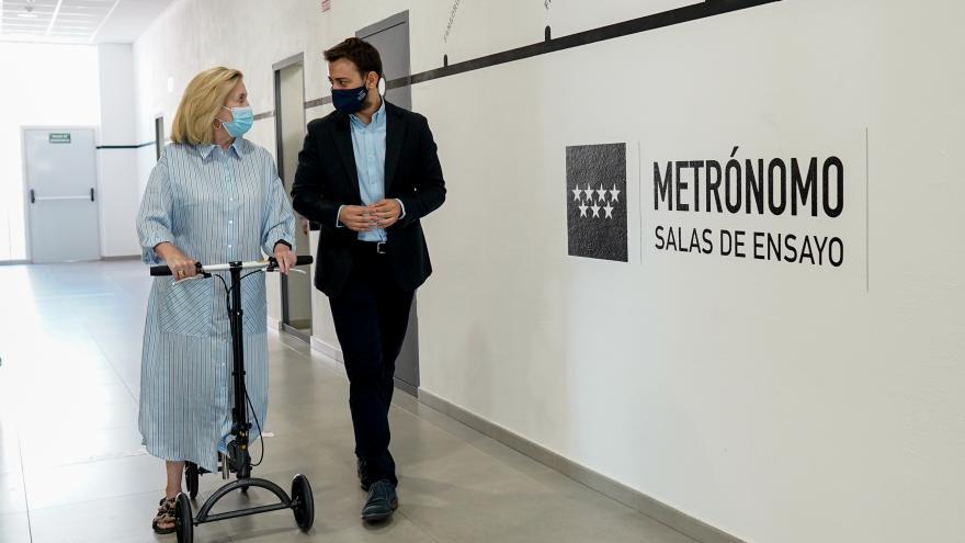 La consejera junto al director general de juventud paseando por un pasillo donde se ve el cartel del entro Metrónomo