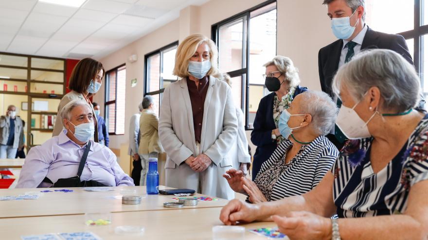 La consejera hablando con personas mayores sentadas en una mesa