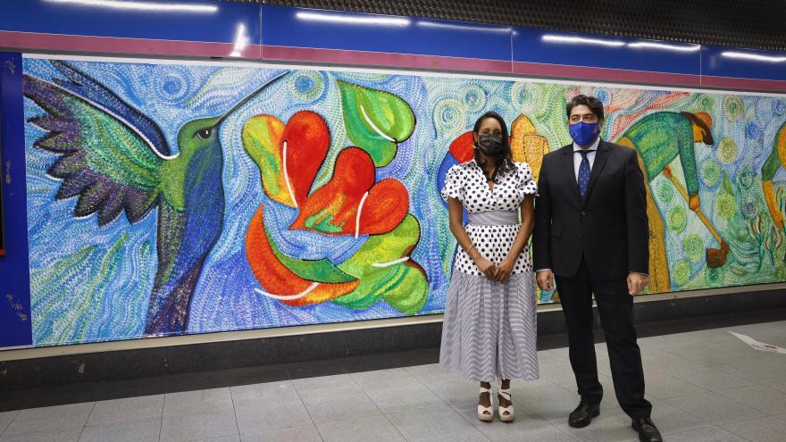 El consejero junto a la artista de los murales posando frente al colorido mural