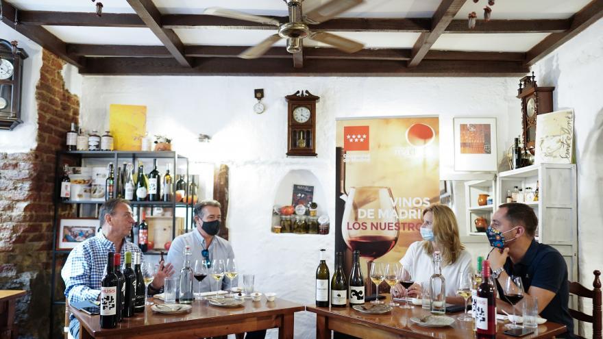 La consejera sentada en una mesa con algunas botellas y copas de vino  junto con el resto de asistentes